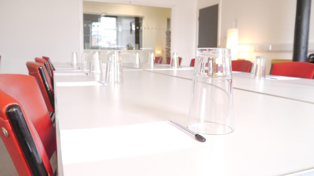 white table with glasses and red chairs